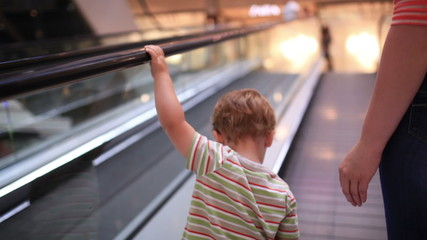 Little boy rises on the escalator