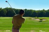 Fototapety Young man swinging golf club, rear view