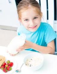 little girl pouring milk