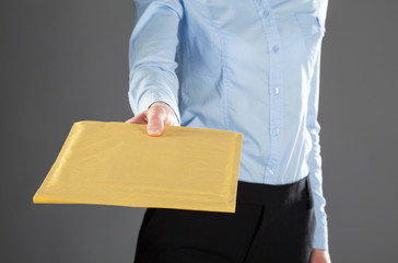 Businesswoman reaching out letter in yellow envelope