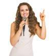Smiling young woman with microphone pointing up on copy space