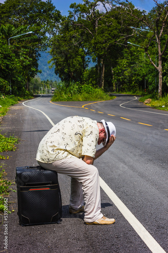 Traveler man in the hat on the road with a suitcase going on res