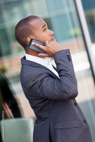 Successful african businessman phoning while smiling