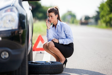 Conceptual photo of woman with a flat tire