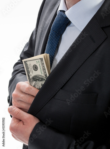 A businessman in a black suit putting money in his pocket