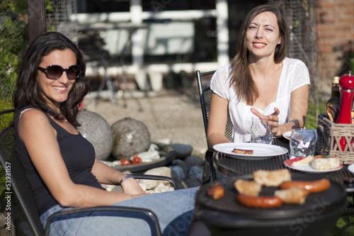 Entspannte Frauen beim Grillen im Garten
