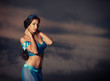 Portrait of a beautiful girl in belly dance costume at sunset