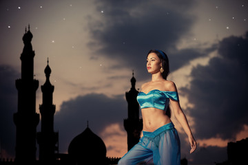 Arabian nights. Girl, silhouette of eastern palace, starry sky