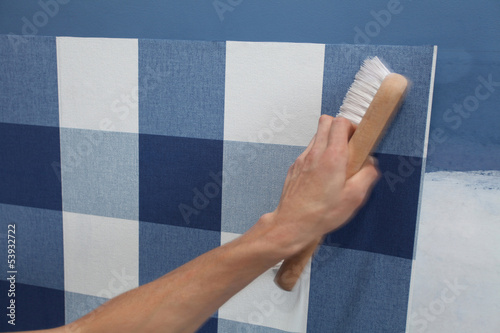 decorator hanging wallpaper with work tool in motion