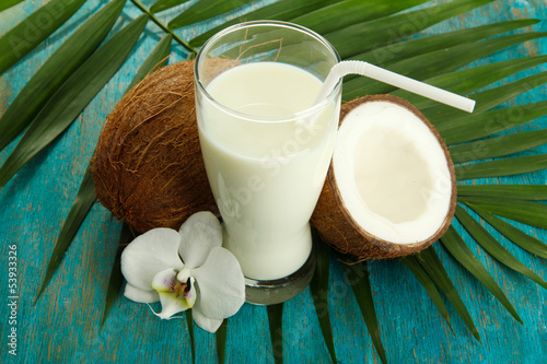 Coconuts with glass of milk,  on blue wooden background