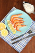 Shrimps with lemon on plate on wooden table close-up