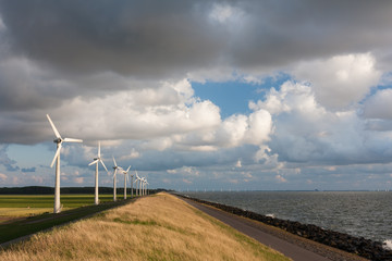 Dutch wind turbines and a cloudscape in the last sunlight of a s
