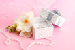 Beautiful box with wedding ring and flower on pink background