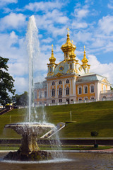 A fontain and a church against blue sky. Peterhof, Russia