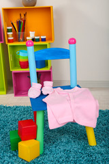 Small and colorful chair with baby clothes