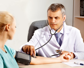 Orthopedic doctor in his office measuring blood pressure