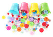 Colorful buttons strewn from buckets isolated on white