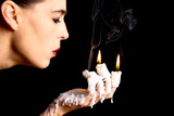 Three candle sticks on fingers buring face blow artistic convers