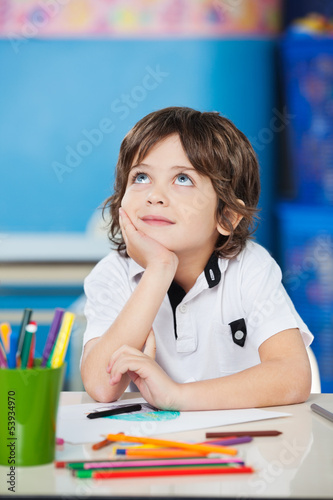 Boy Looking Up While Sitting With Hand On Chin At Desk