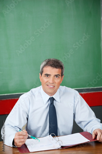 Professor With Binder And Pen Sitting At Desk
