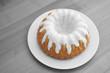 Kuchen mit Zuckerguss auf Teller und Holztisch