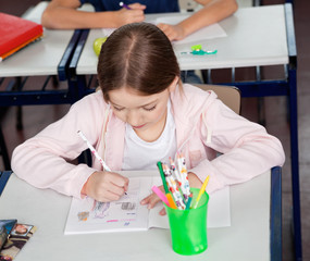 Schoolgirl Drawing At Desk In Classroom