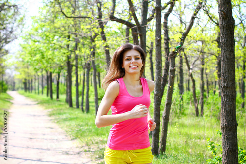 Attractive young woman running in summer park