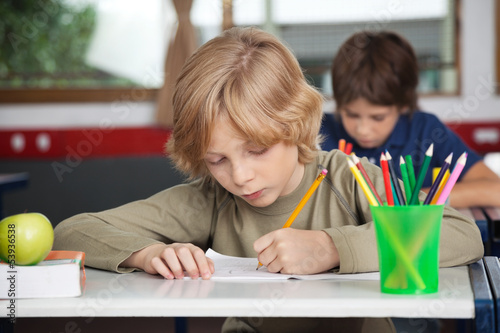Schoolboy Writing In Book At Desk