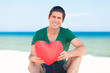 man with shape heart at the beach
