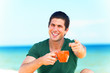 Handsome young man with cup at beach background