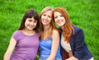 Redhead, brunette and blonde girl sitting at green grass in the
