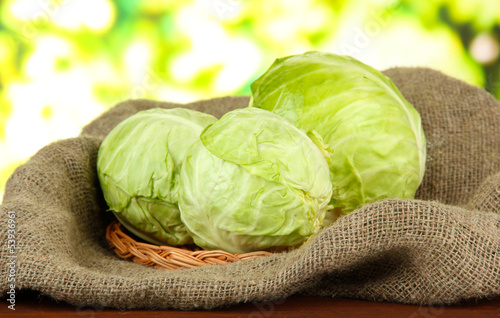 Green cabbage on wicker mat and sackcloth, on bright background