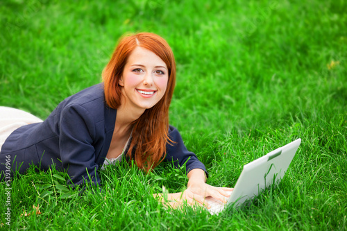 Redhead girl at green grass with notebook