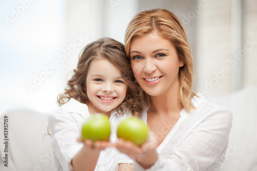 mother and daughter holding green apples