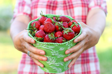 Young woman with a green pail of strawberries close-up
