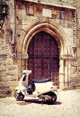 White vintage scooter near medieval gate