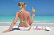 Girl with a glass of orange on the beach of Exuma, Bahamas