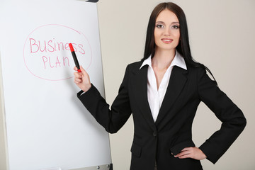 Businesswoman presenting on whiteboard.