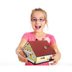 Mädchen mit Miniatur Haus lacht vor Freude