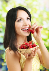 Girl with fresh cherries on natural background