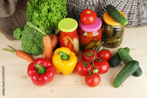 Fresh vegetables and canned on wooden table close up