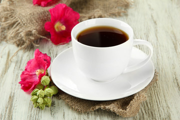Cup of coffee and pink mallow flowers on wooden background