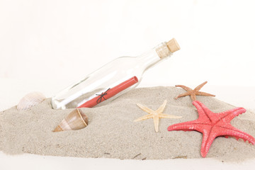 Glass bottle with note inside on sand, on white background