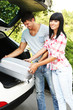 Portrait of happy beautiful couple putting suitcase into car