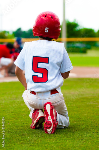Kneeling baseball boy for injured player