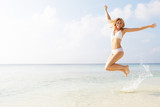 Woman Jumping In The Air On Tropical Beach