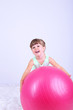 Little cute girl playing with big ball, on gray background