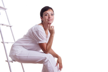 Happy woman sitting on step ladder