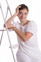 Smiling woman sitting on step ladder