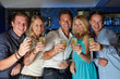 Group Of Friends Enjoying Glass Of Champagne In Bar